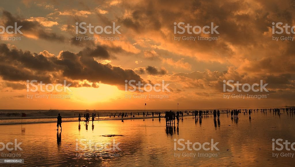 stormy sunset, people on the beach stock photo