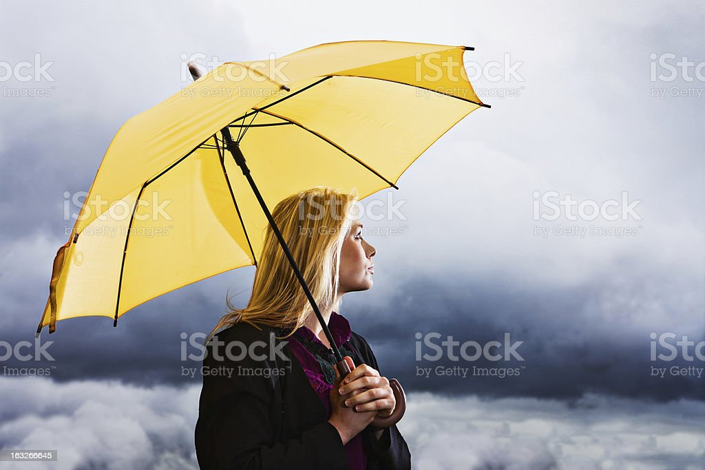 Stormy weather: wistful blonde with yellow umbrella waits out thunderstorm royalty-free stock photo