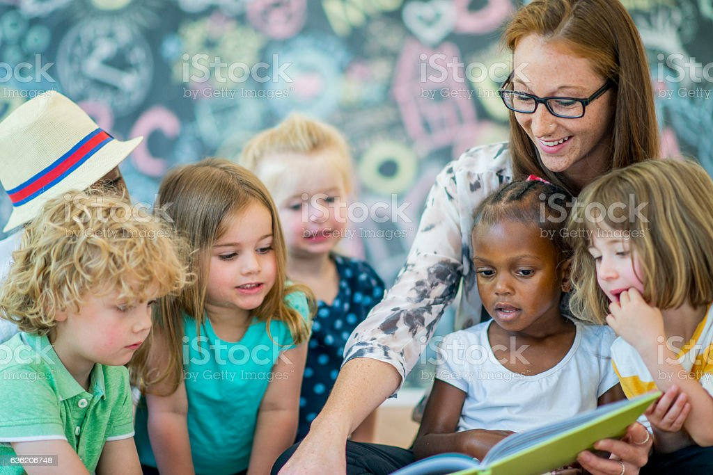 A teacher is reading a book to her preschool students.