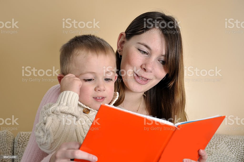 Story time: Young Mother Reading Book to Son royalty-free stock photo