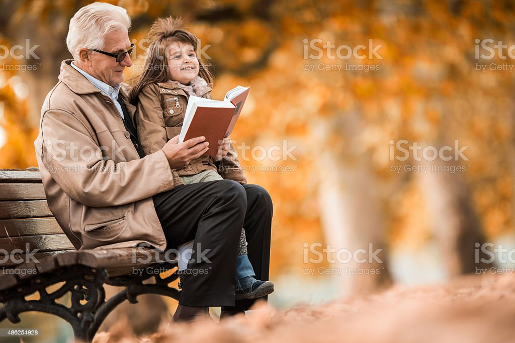 Storytelling during autumn day at the park. stock photo
