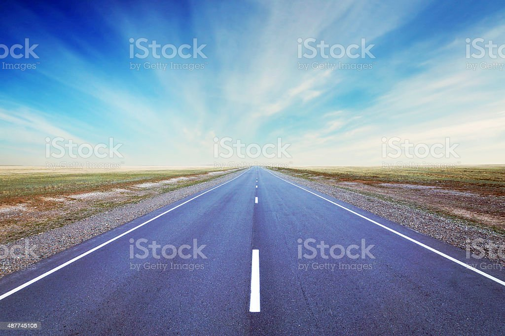 Straight as an arrow road goes at the wide plain stock photo