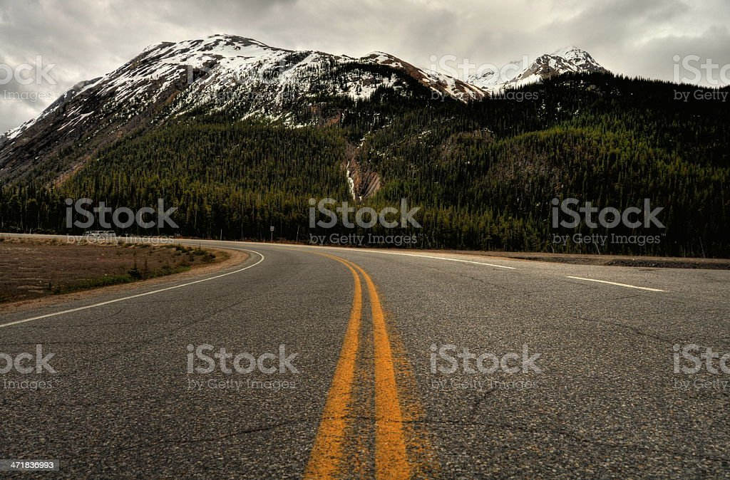 Straight asphalt road going in the wood and mountain stock photo