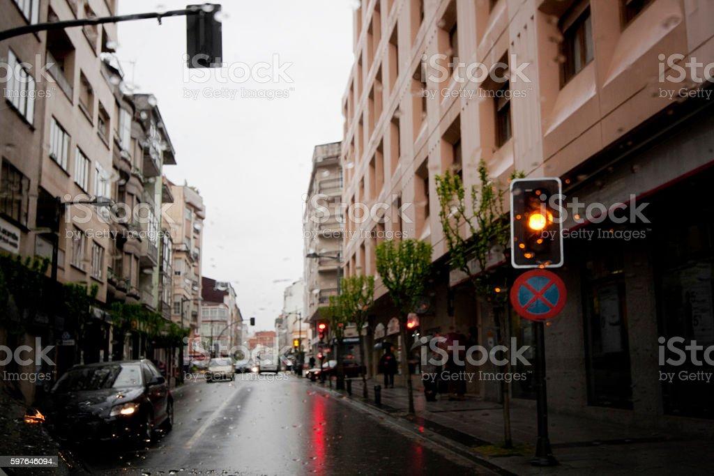 Straight city street view in rainy day , amber traffic light. stock photo