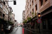 Straight city street view in rainy day , amber traffic light.