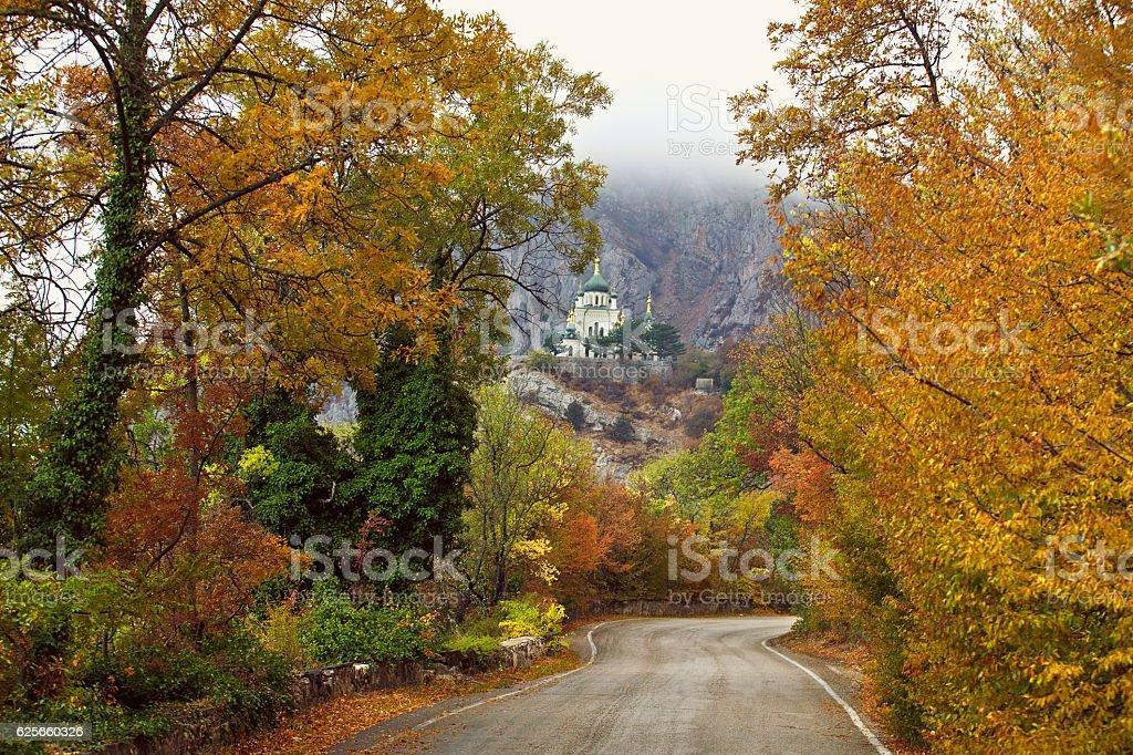 Straight mountain road through autumn woods to the church stock photo