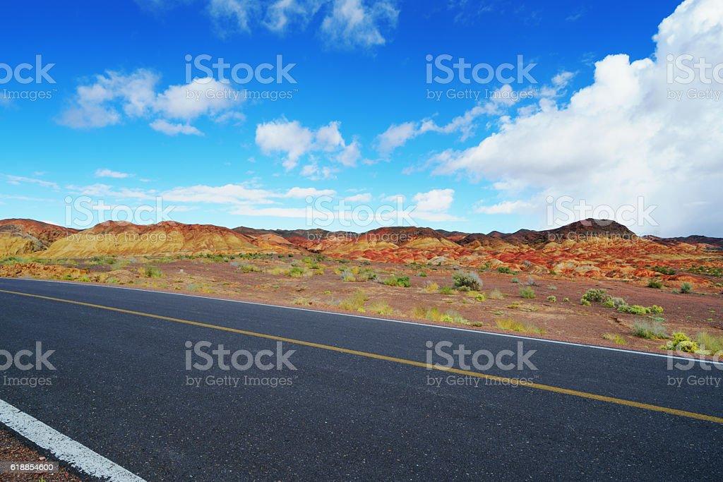 Straight road along the Danxia landform in Xinjiang, west China stock photo