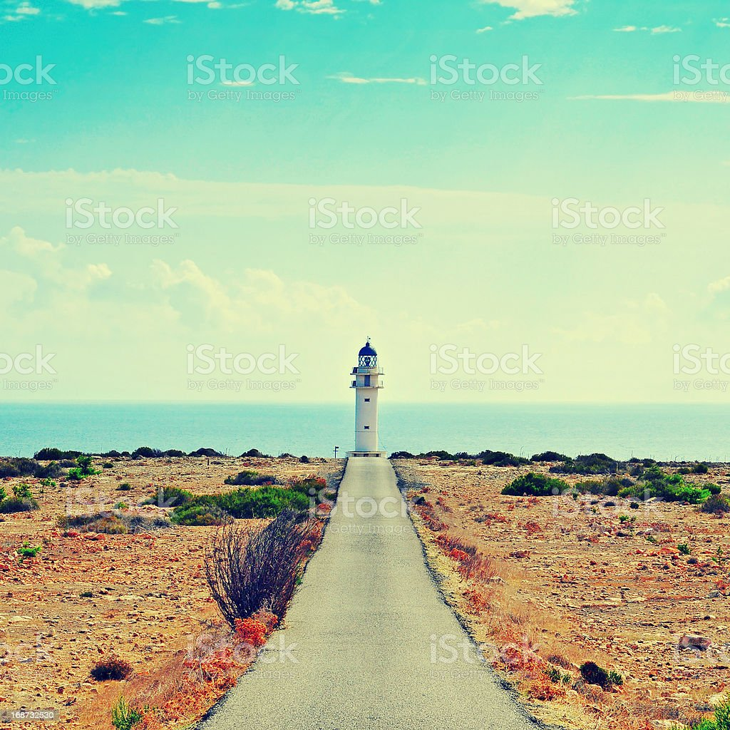 Straight road leading to a lighthouse in Formentera, Spain stock photo