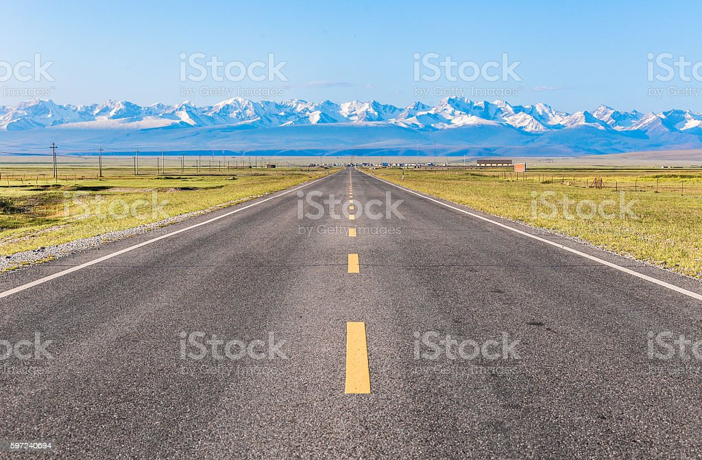 Straight road under the snow mountain. stock photo