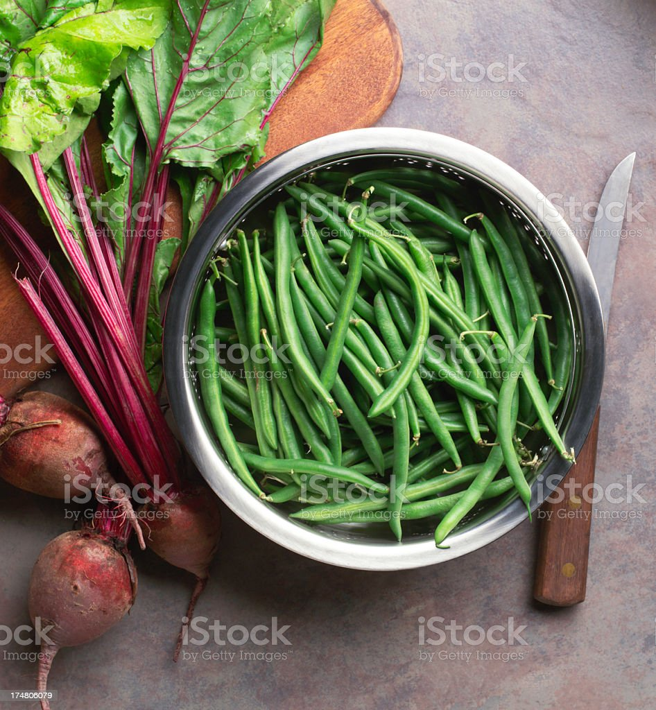 Strainer full of fresh green beans next to fresh radishes stock photo