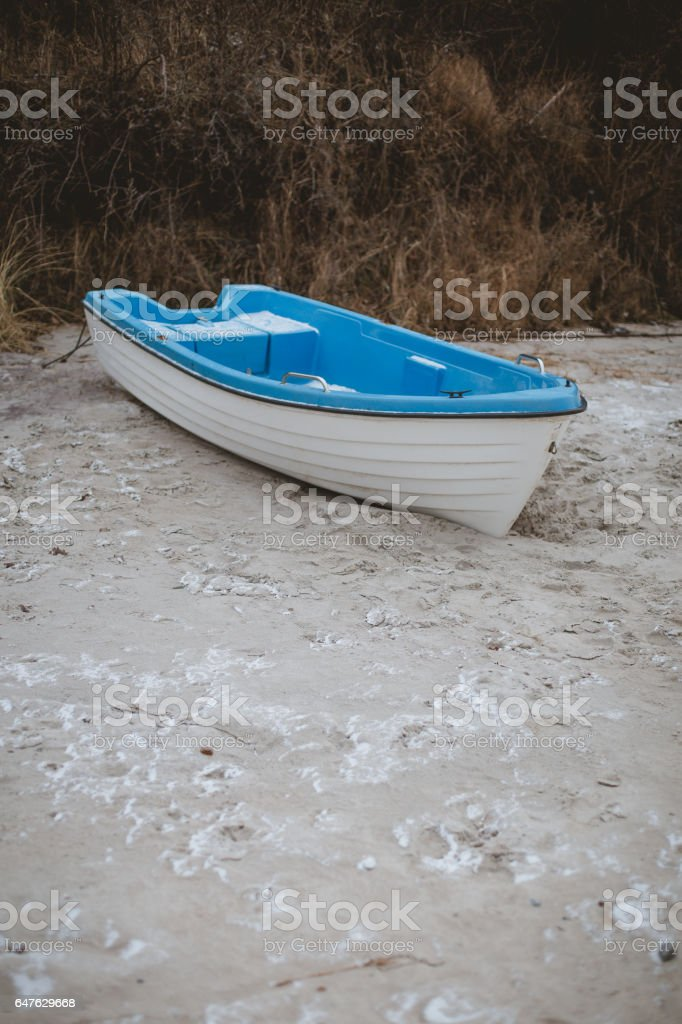 Stranded blue boat on a snowy beach stock photo