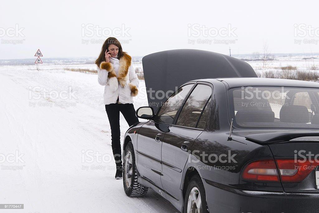 Stranded woman in snow with broken down car with bonnet up royalty-free stock photo