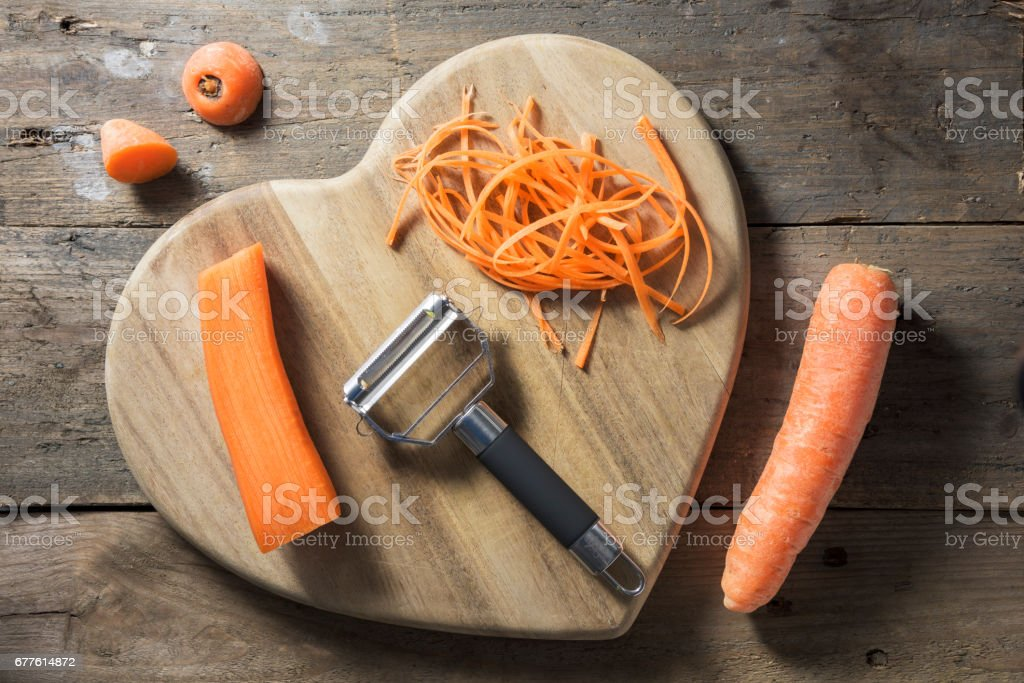 Strands of julienned carrot on a heart shaped chopping board stock photo