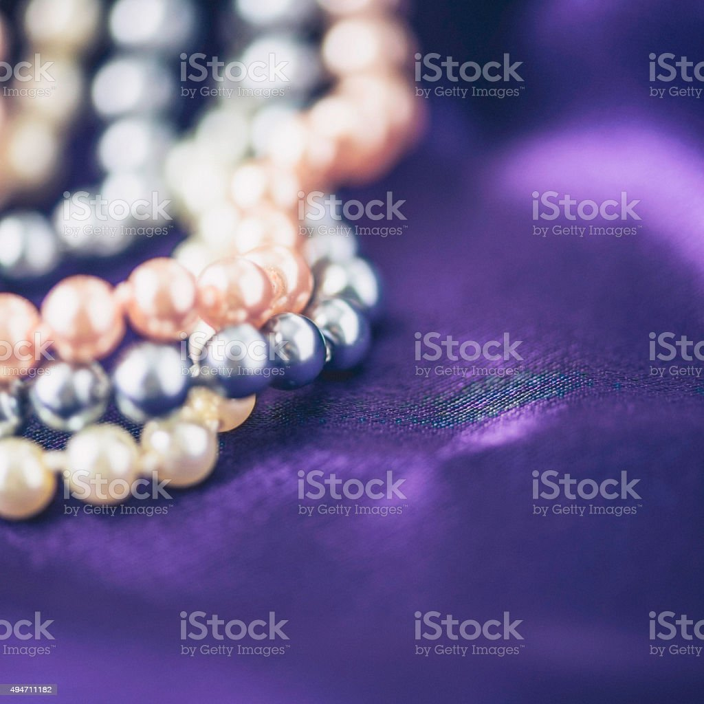 Strands of pearl jewelry on rich purple satin stock photo