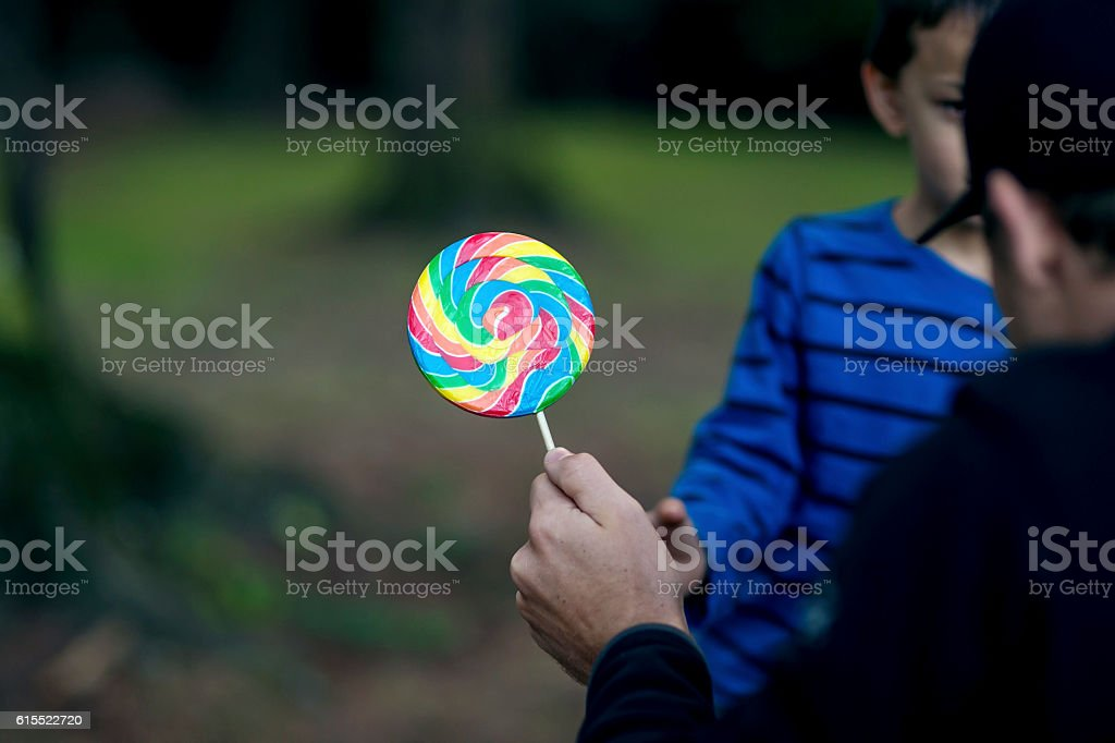 Strange adult male offering a young boy a lollipop stock photo