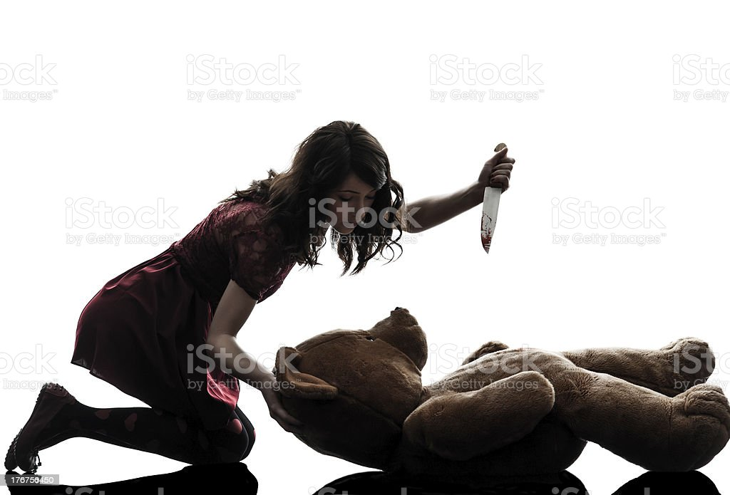 strange young woman killing her teddy bear silhouette stock photo