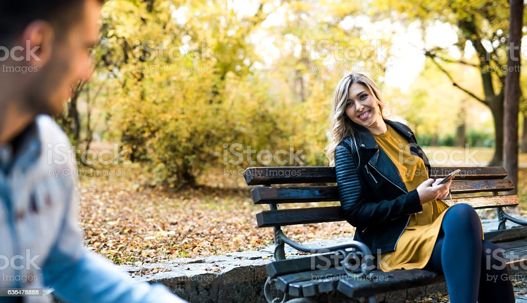 Stranger suducing a beautiful girl in the park stock photo