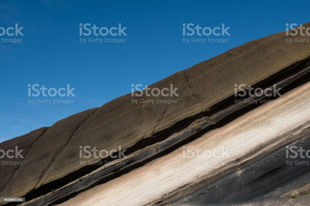 stratified, striped rocks  , colored  stone sediment stock photo