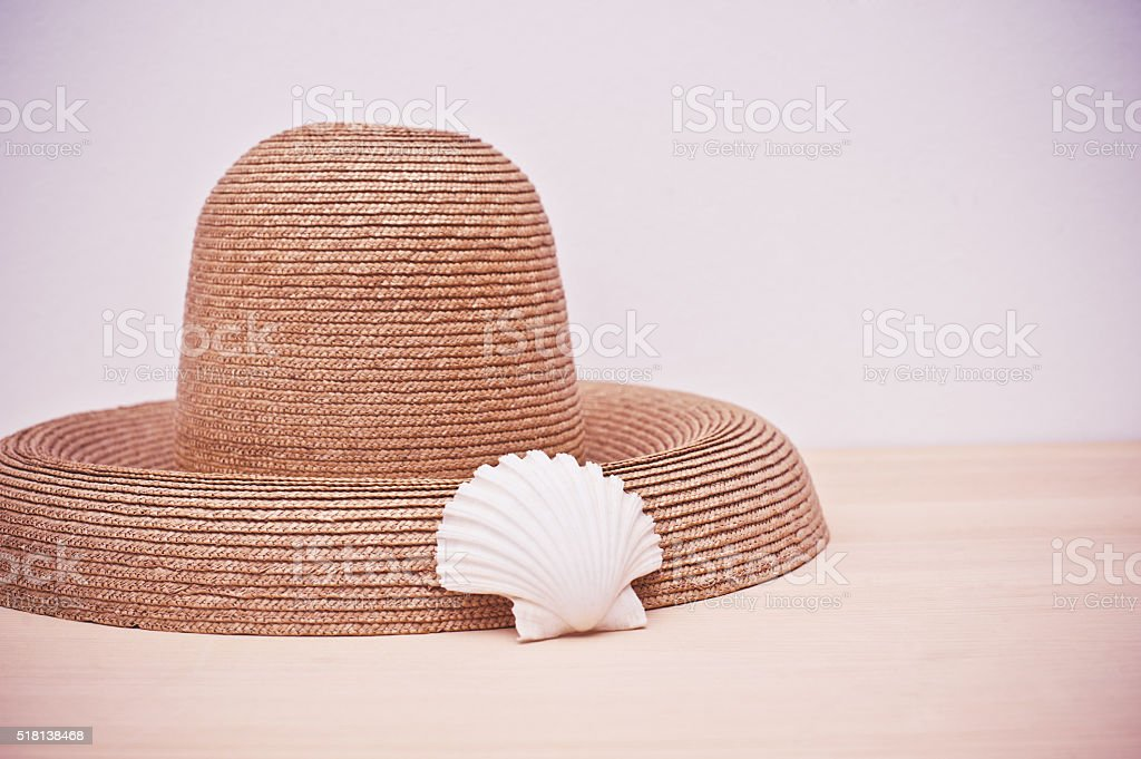 Straw hat and seashell on wooden floor stock photo