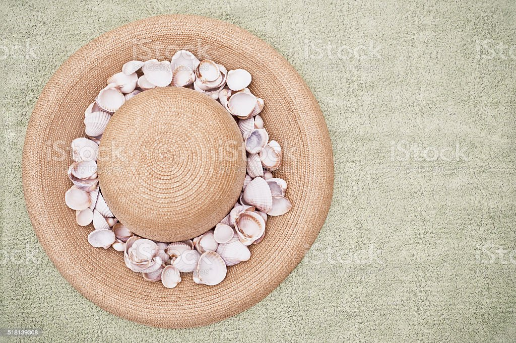 Straw hat and seashells on green towel stock photo