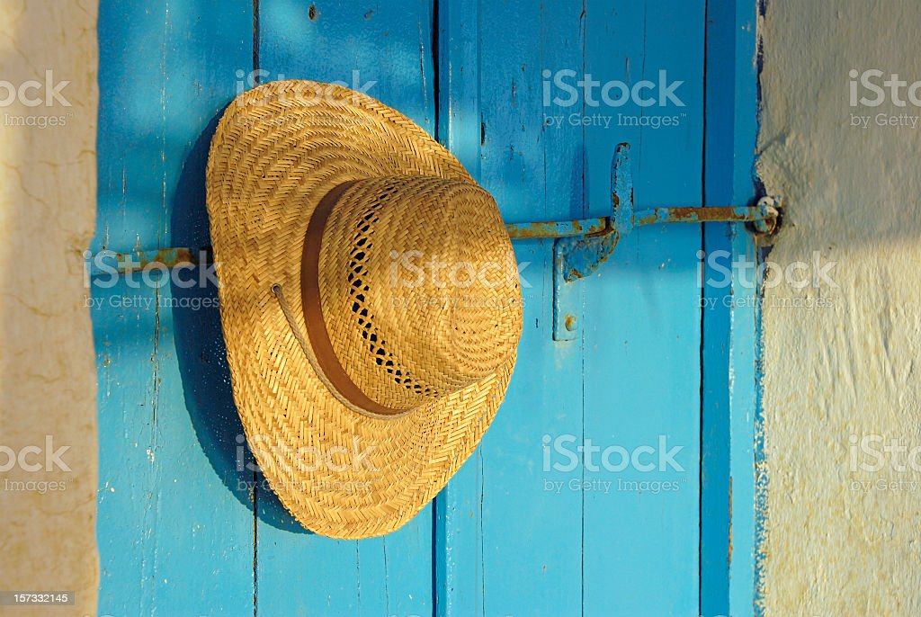 Straw hat on a blue door in the evening sun. royalty-free stock photo