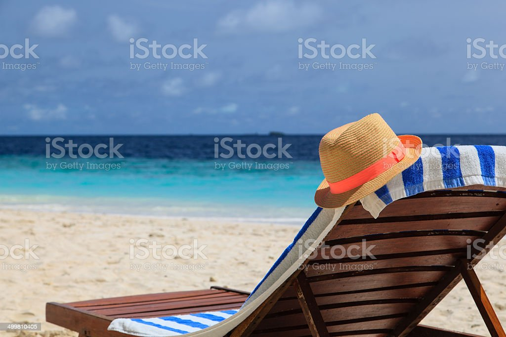 straw hat on a lounge chair at tropical beach stock photo