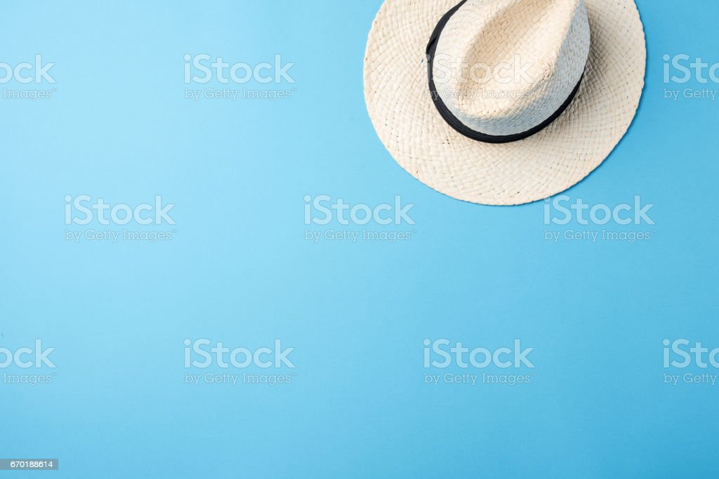 Straw hat on blue background stock photo