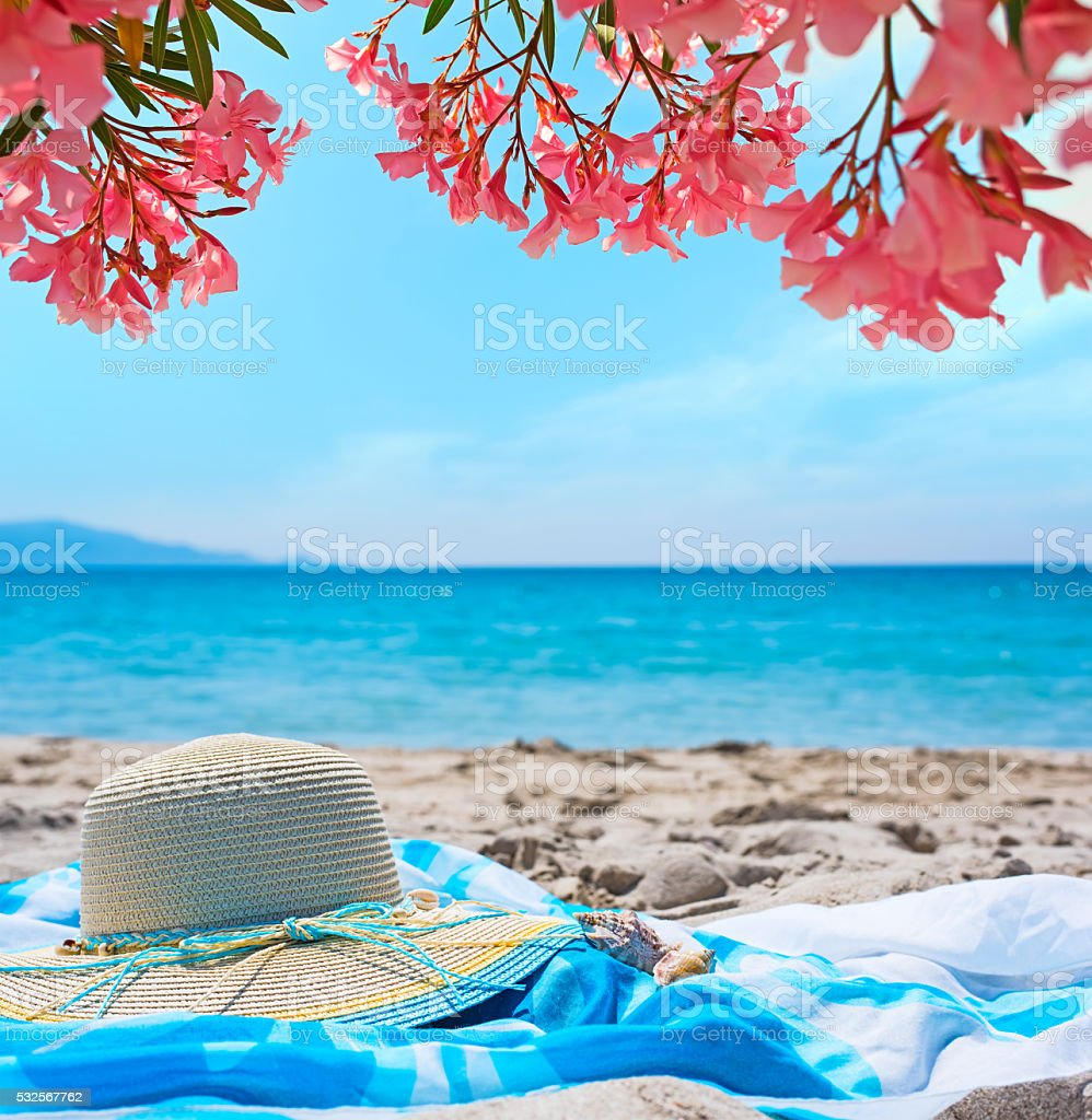 straw hat on the sand stock photo