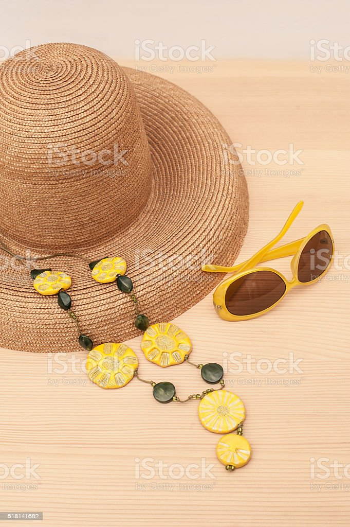 Straw hat, yellow sunglasses on wooden floor stock photo