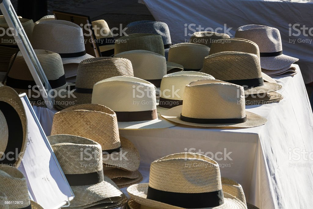 Straw hats in a market exposed stock photo