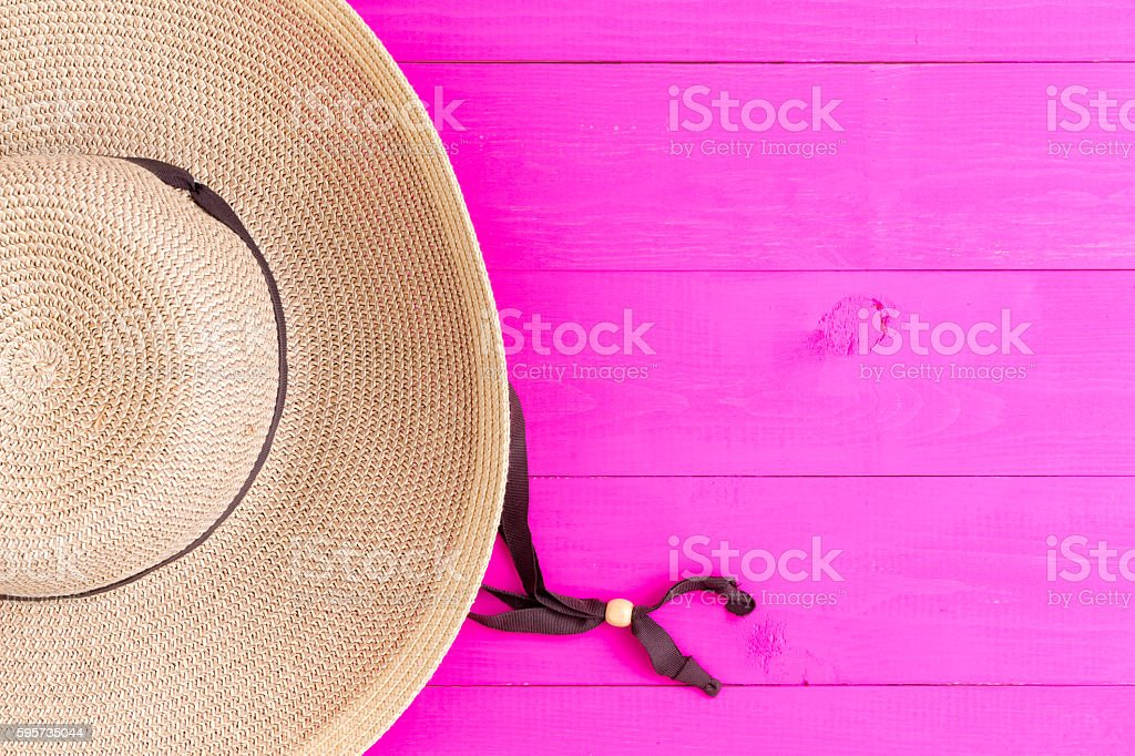 Straw sunhat on vibrant pink background stock photo