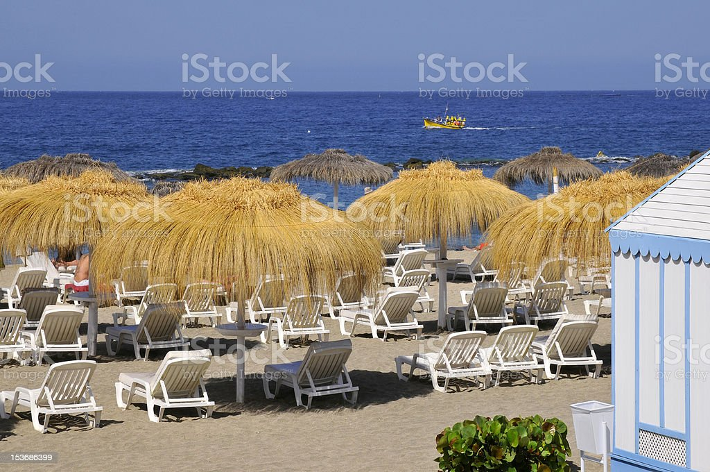 Straw umbrella and deckchairs at Tenerife royalty-free stock photo