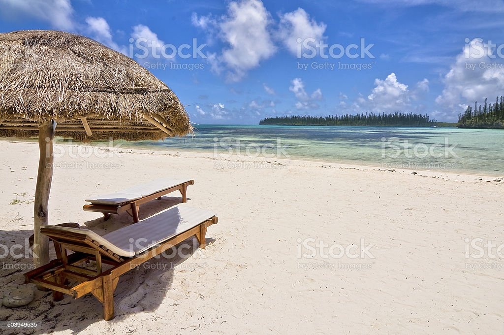 Straw umbrella and wooden chairs on a beach stock photo