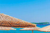 Straw umbrella on beautiful beach background