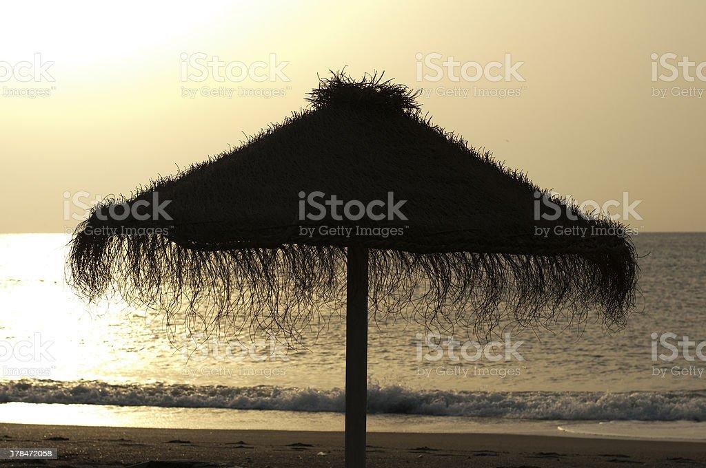 Straw umbrella on sunrize stock photo
