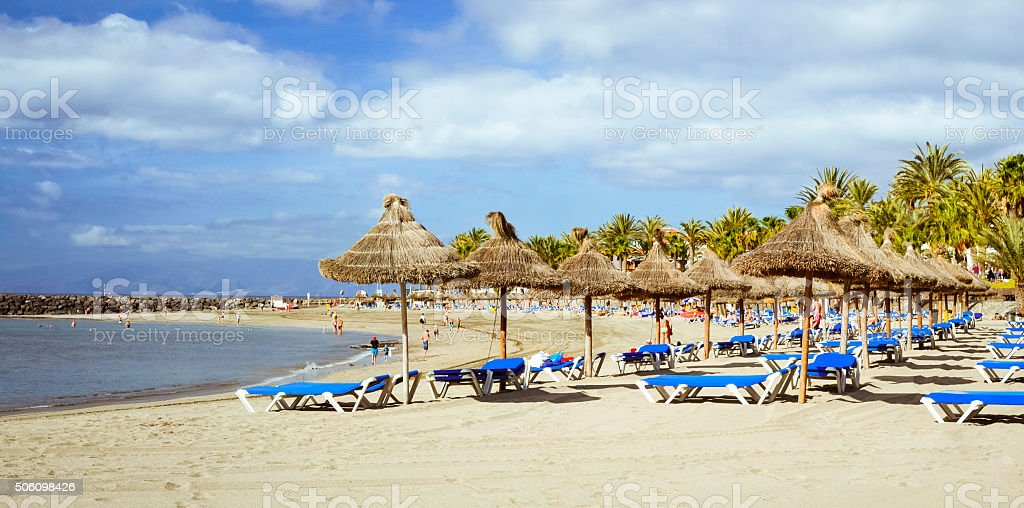 Straw umbrellas and loungers on the Playa de Las Americas stock photo