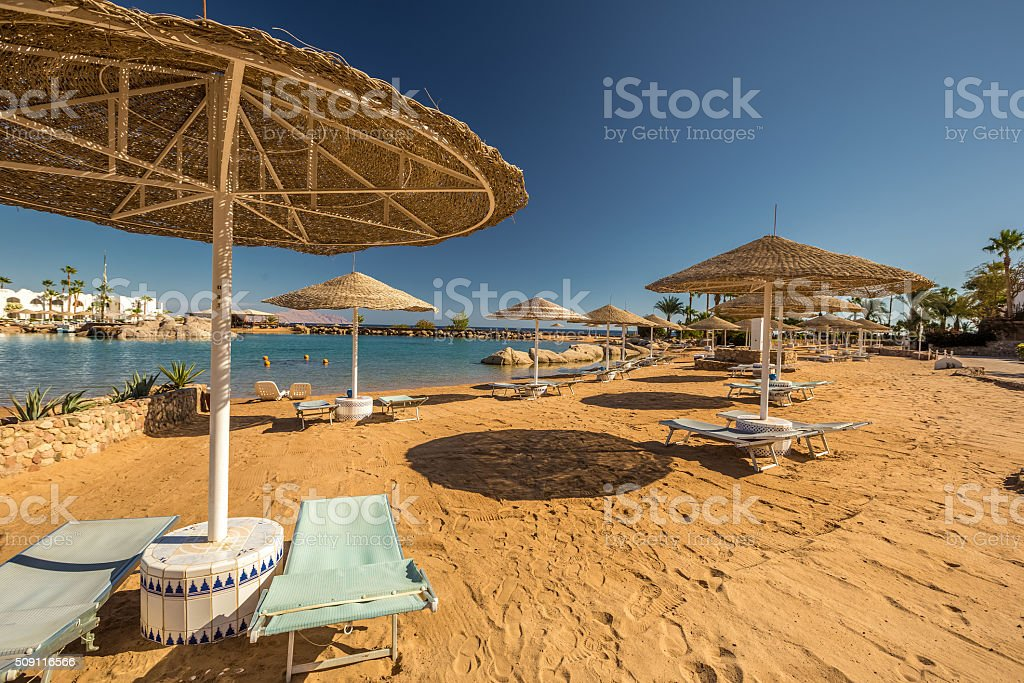 Straw umbrellas and sunbeds on the wonderful tropical beach. stock photo