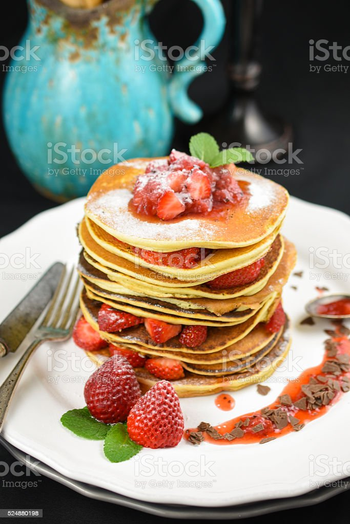 Strawberrie pancakes on black wallpaper whit a chocolate stock photo