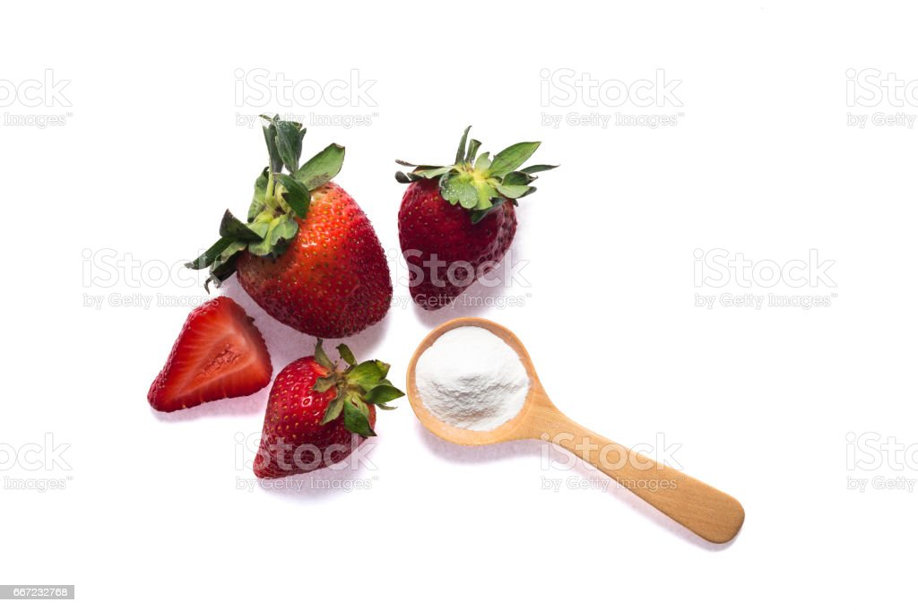 Strawberries and baking soda in wooden spoon stock photo