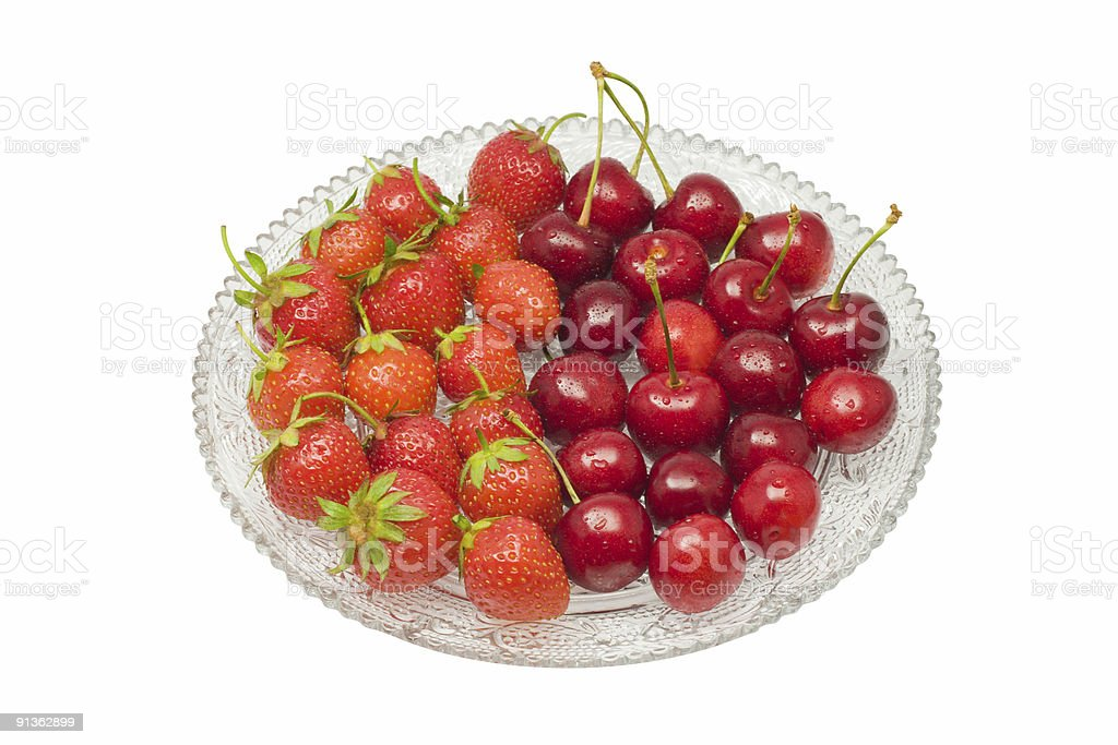 Strawberries and cherries upon glass dish, isolated, clipping path stock photo