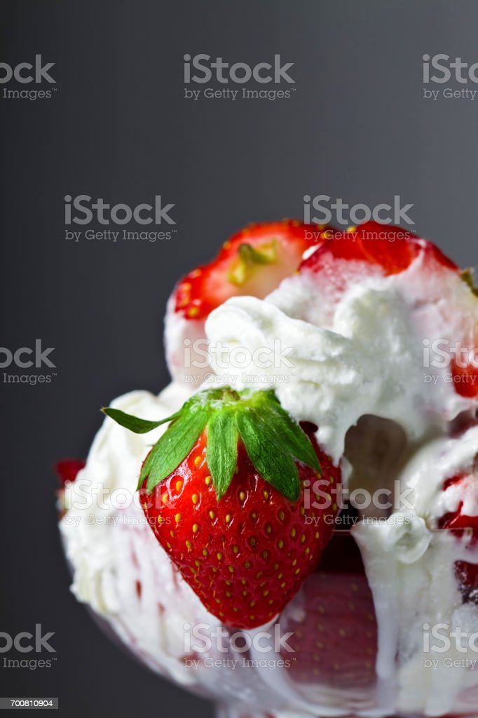 Strawberries and cream in glass bowl stock photo