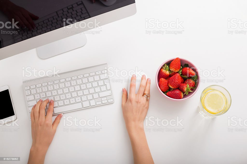 Strawberries and lemon water on office table stock photo