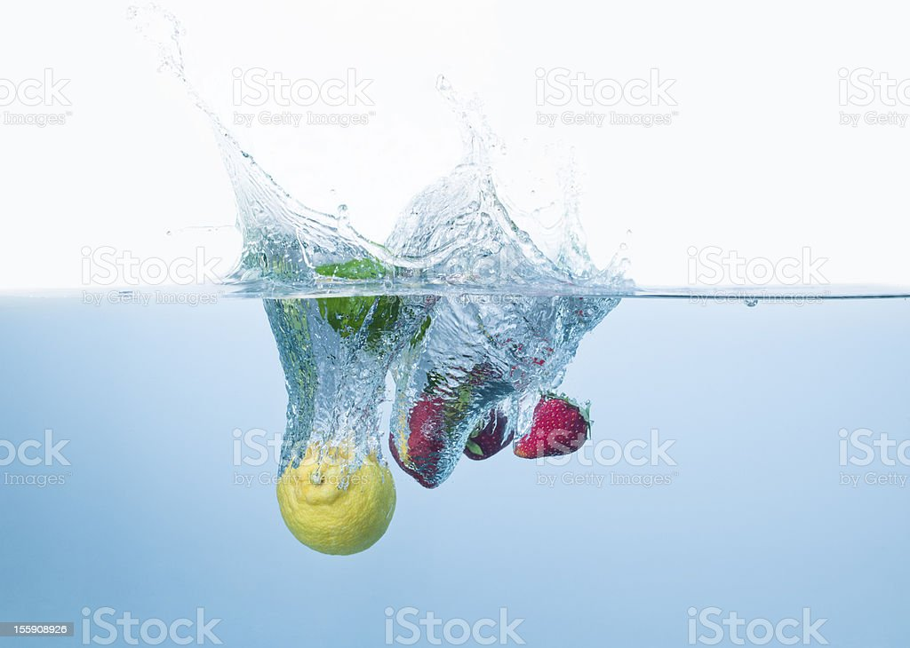 Strawberries and lemons cocktail splashing into the water royalty-free stock photo