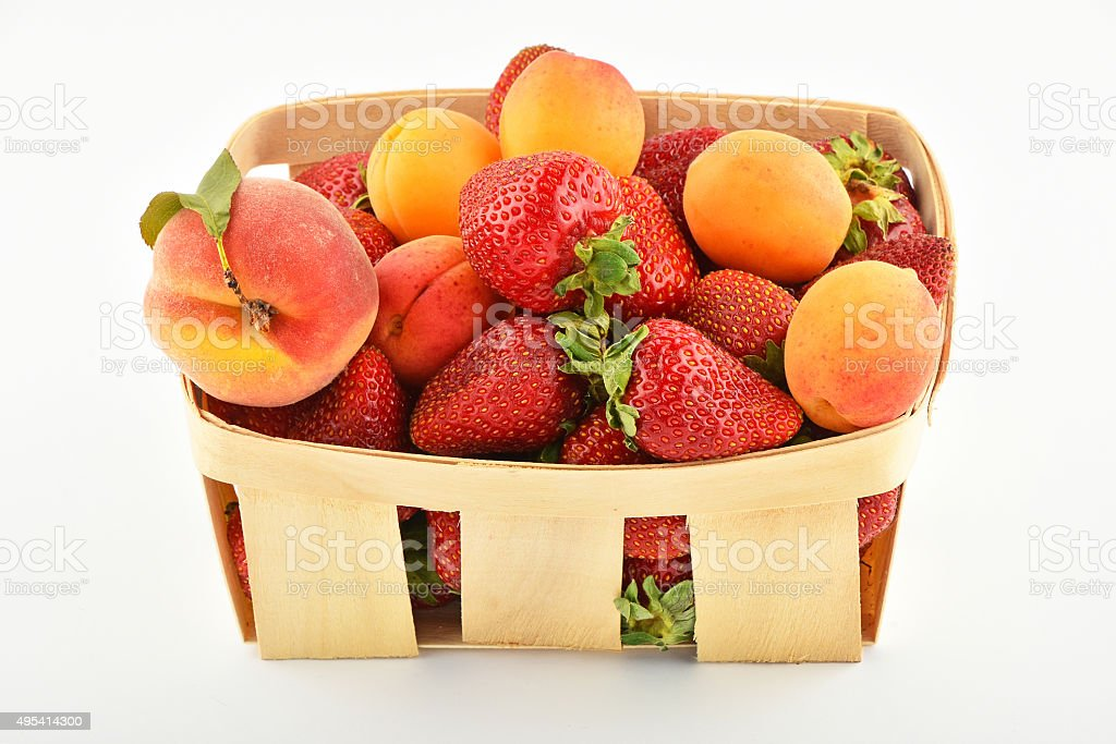 Strawberries, apricots and peach in wooden basket isolated on white royalty-free stock photo