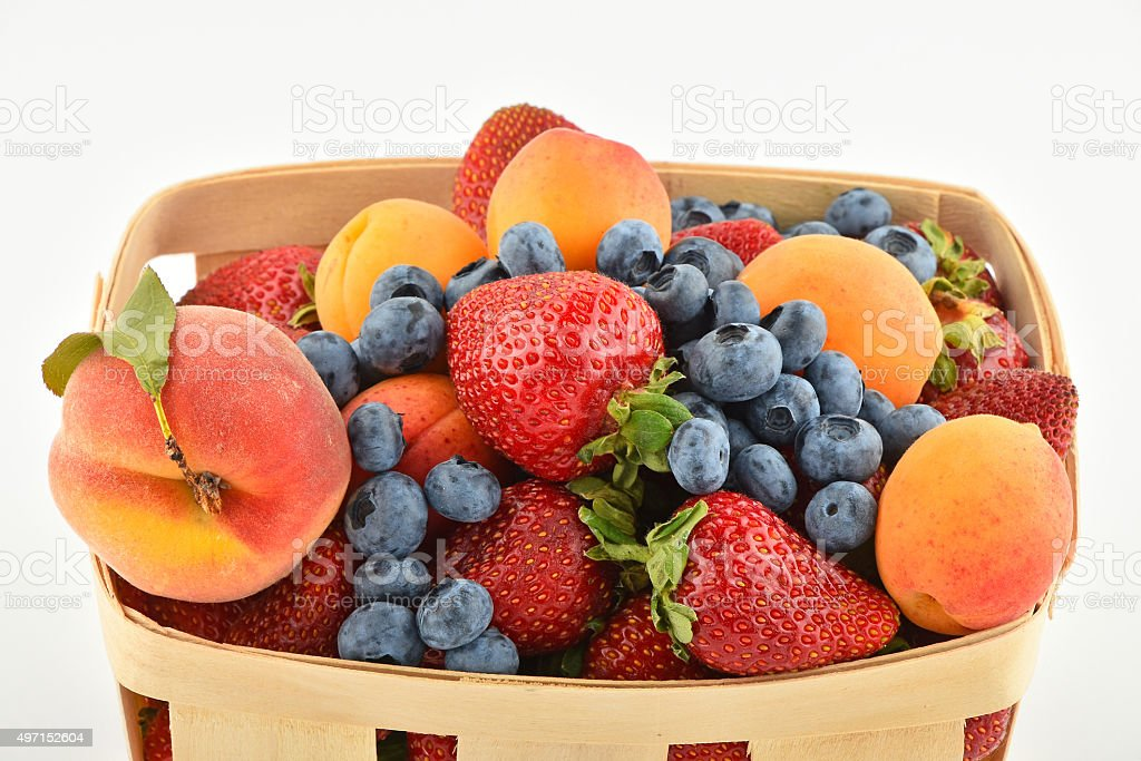 Strawberries, apricots, blueberries, peach in basket isolated on royalty-free stock photo
