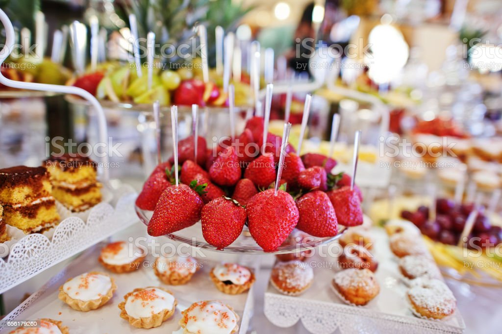 Strawberries at wedding reception table with different fruits, cakes and swee stock photo