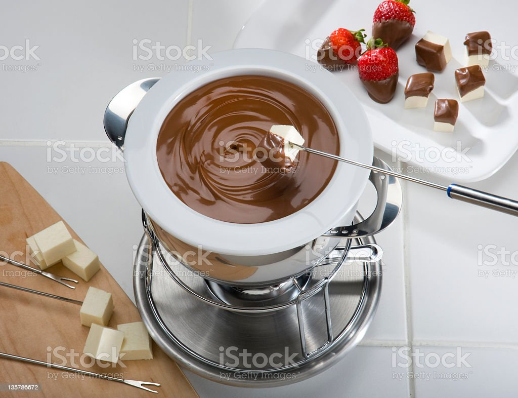 Strawberries being dipped into chocolate fondue stock photo