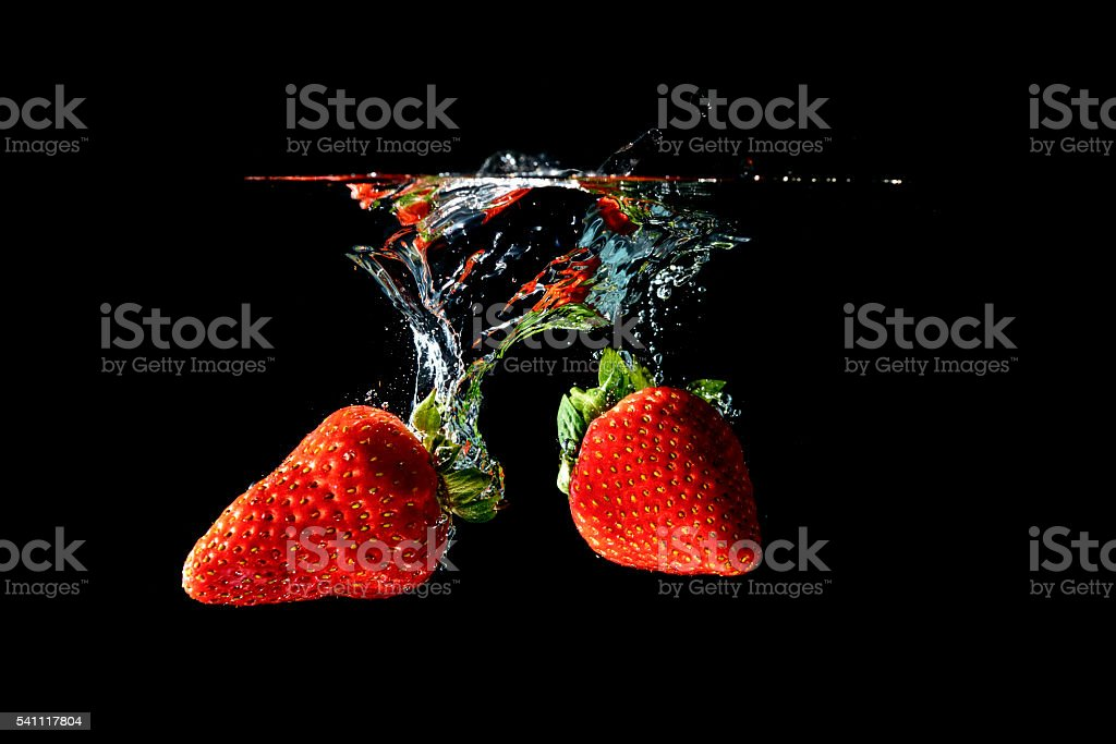 Strawberries falling into water stock photo