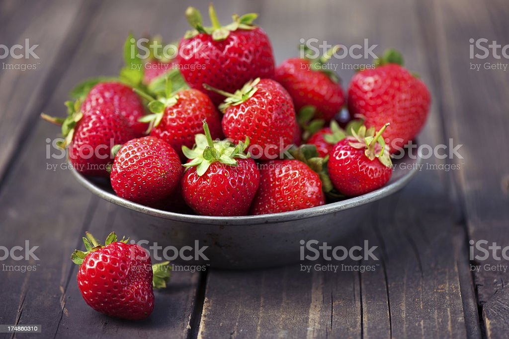 Strawberries in a bowl on rustic wood stock photo