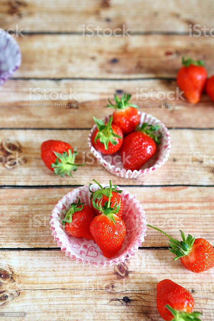Strawberries in paper forms for cupcakes stock photo
